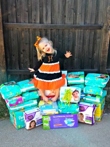 Harrison atop the diaper mountain that was donated at her birthday (and 5 boxes came in after the pic!) - Oct 2014